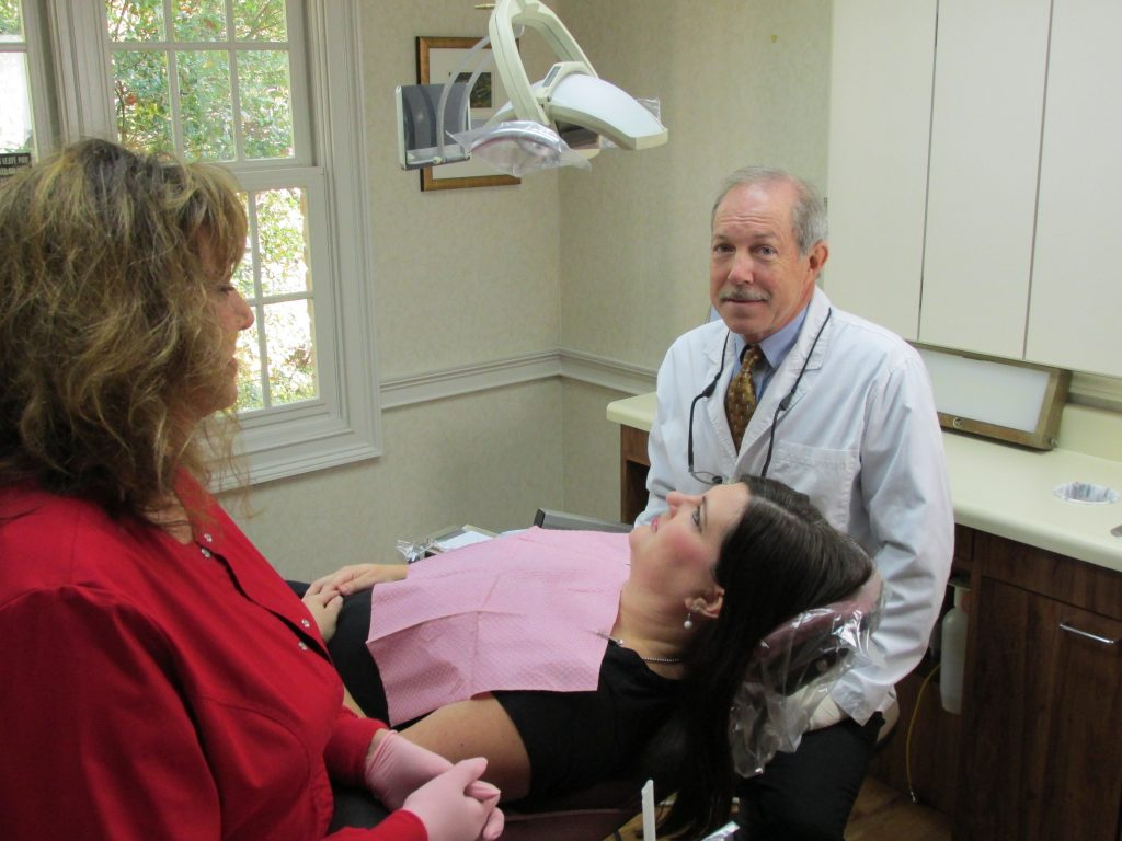 Dr. Rice, cosmetic dentist athens ga, preparing for aesthetic dentistry services with patient and assistant