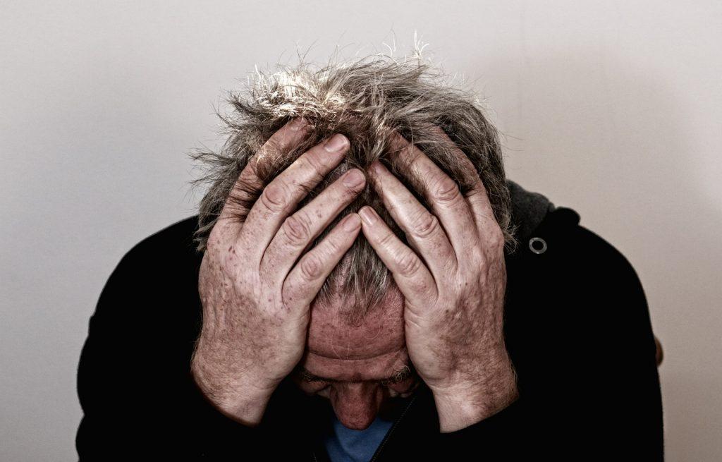TMJ screenings, TMJ symptoms, man with headache and head in hands